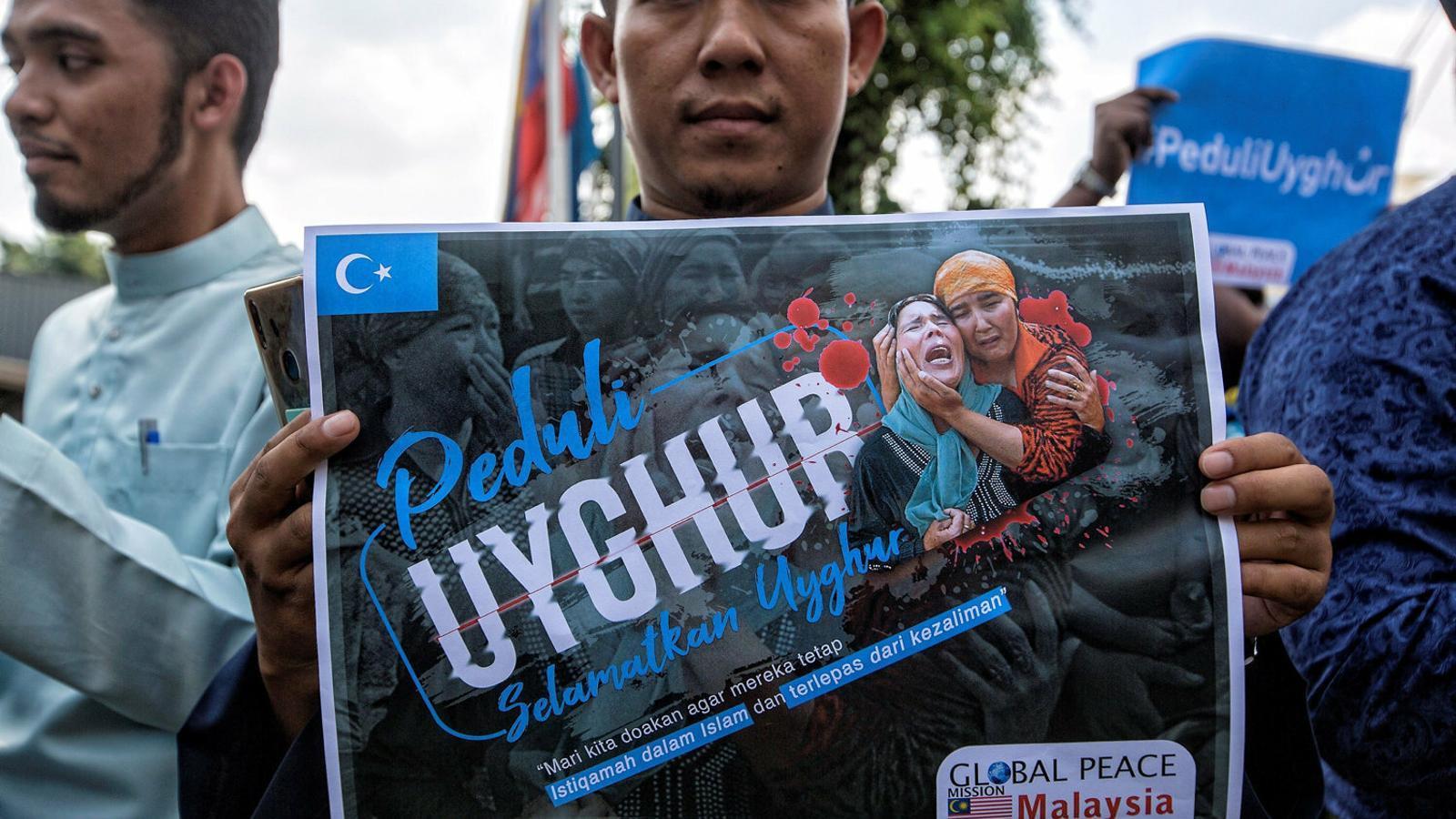 """Un activista mostra una pancarta en què demana que se """"salvin els uigurs"""" durant una protesta a Kuala Lumpur el 5 de juliol."""