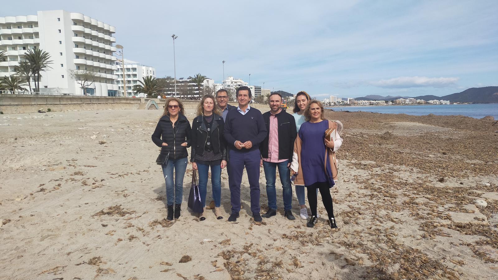 Representants del PP sobre la platja de Cala Millor, despullada d'arena.