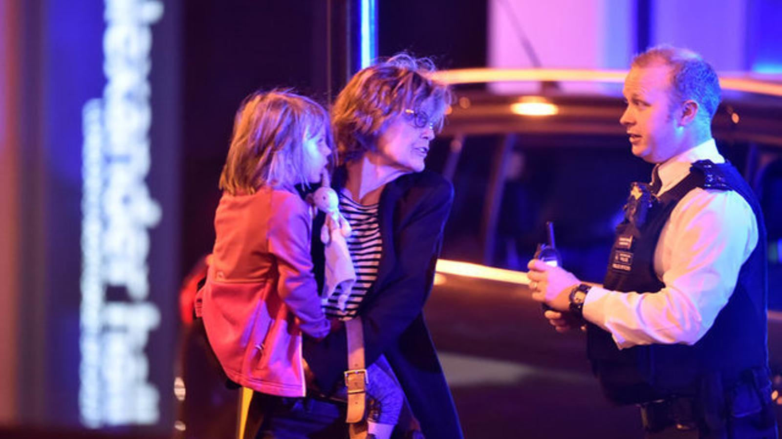 Un agent aconsella una dona a buscar un lloc segur fora de l'àrea dels incidents. / HANNAH MCKAY / REUTERS