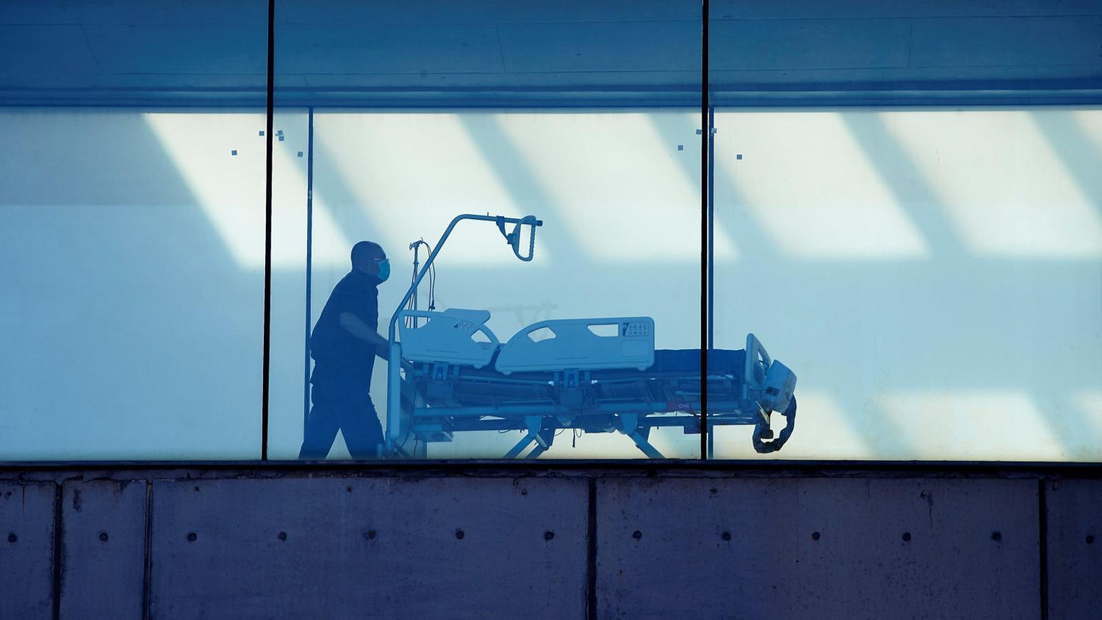 Un zelador ahir portant una camilla a l'Hospital de Bellvitge, poc després de l'aval del TSJC a les restriccions del Govern.