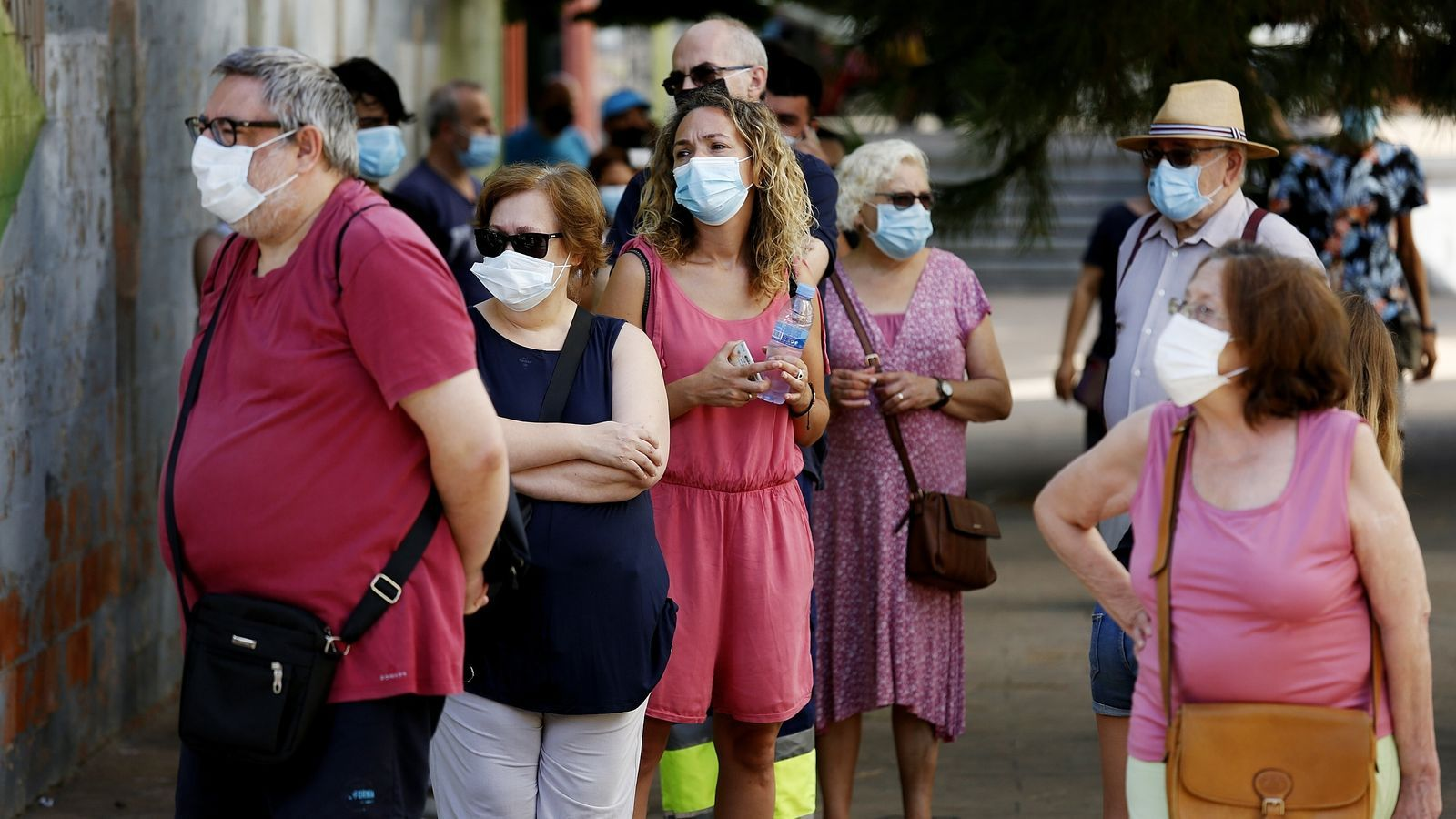 Un grup de persones respectant les distàncies de seguretat i portant mascareta, en un cribatge massiu de Barcelona.