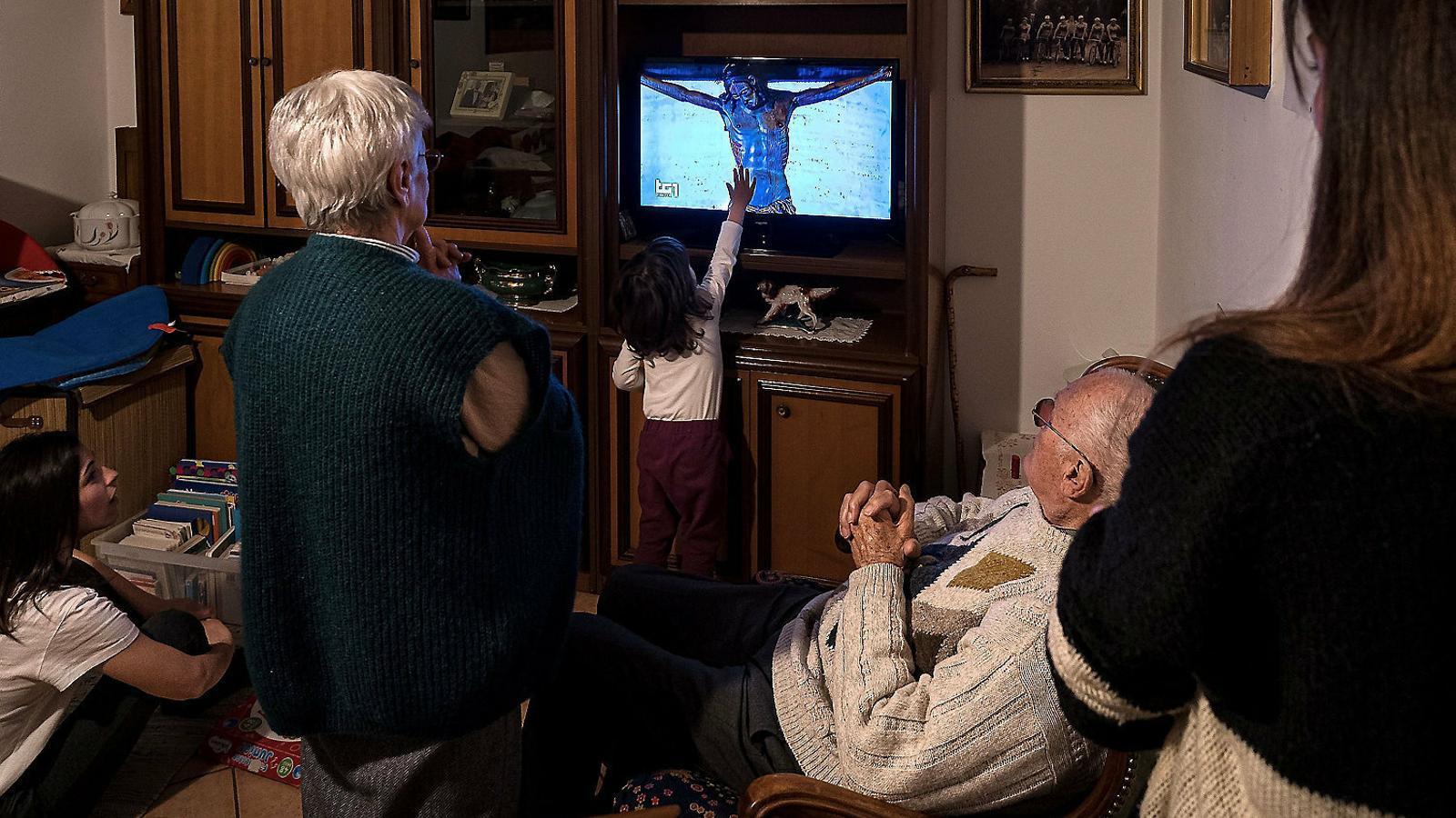 Una família italiana confinada seguint la missa del papa Francesc  per la televisió.