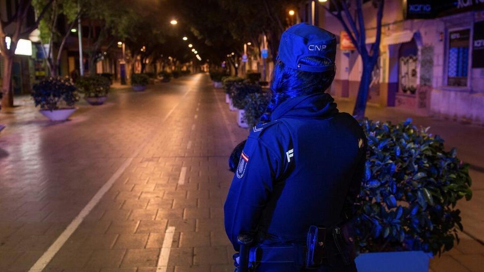 Un policia vigila el compliment del toc de queda en el carrer Blanquerna de Palma