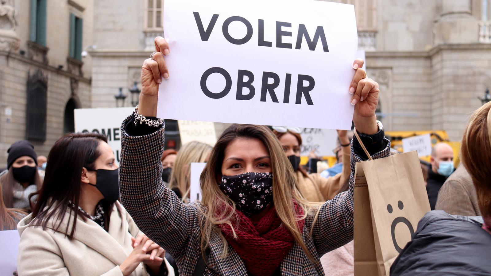 Una manifestant en la protesta d'aquest dimecres a la plaça Sant Jaume de Barcelona per reclamar l'obertura dels centres comercials