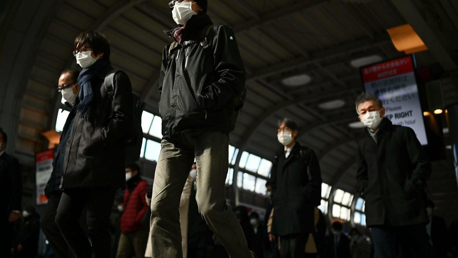 Treballadors equipats amb mascaretes en hora punta a Tòquio