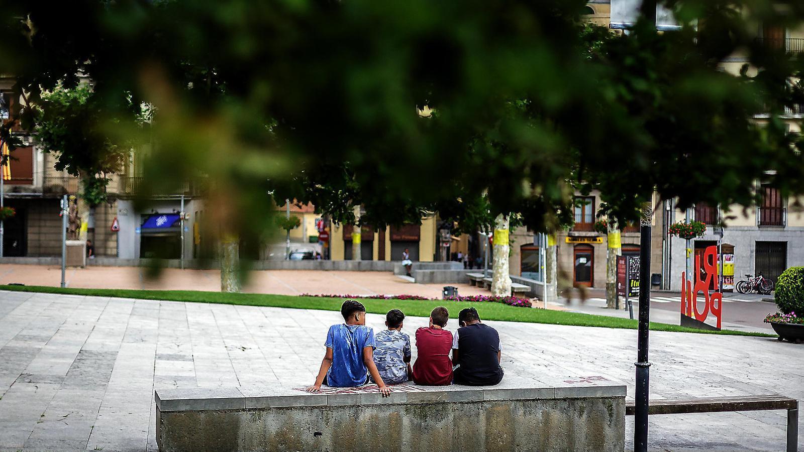 Quatre nois asseguts en un banc de Ripoll, on vivien els nou joves de la cèl·lula terrorista dels atacs del 17-A.