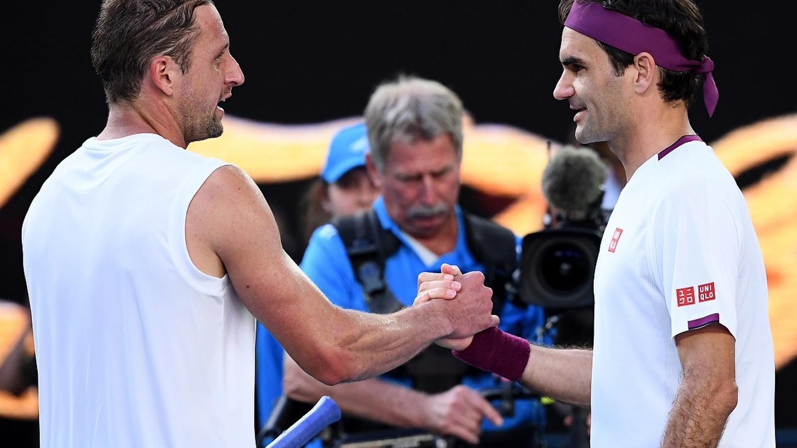 Tennys Sandgren i Roger Federer es saluden després del partit que els ha enfrontat a l'Open d'Austràlia