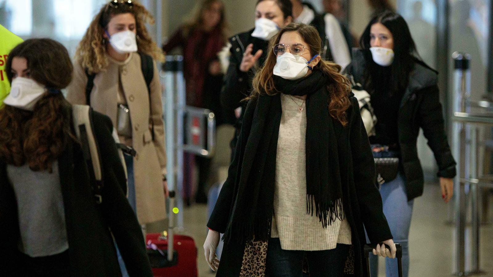 Viajeros procedentes de Italia protegidos con mascarillas a su llegada al aeropuerto de Manises