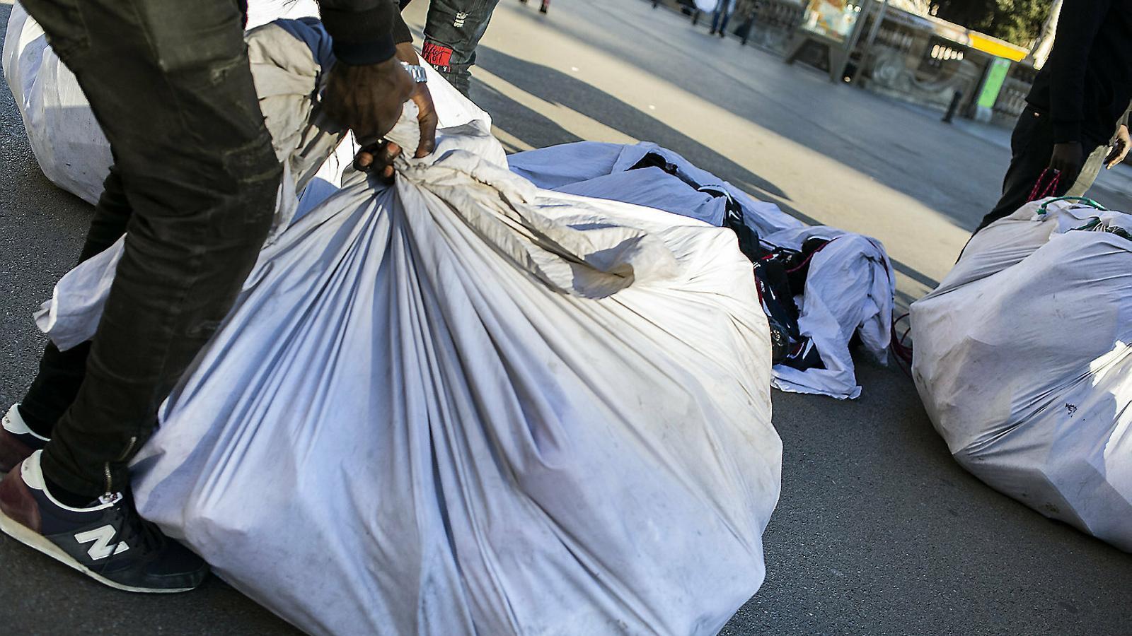 Uns venedors ambulants recollint el seu material per la presència de la policia.