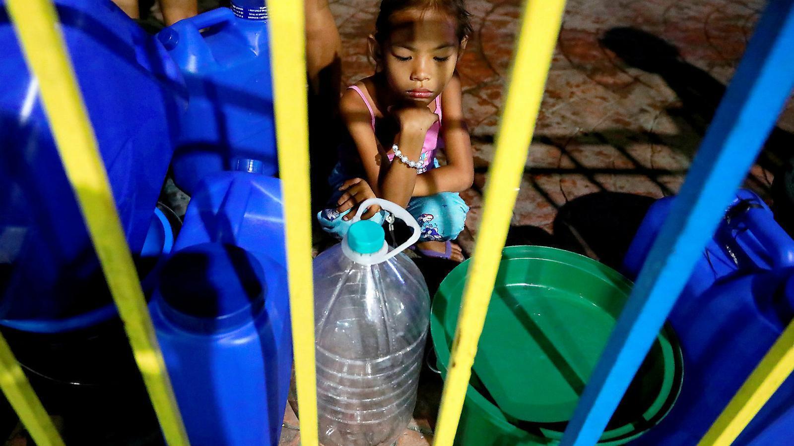Una nena mira com la seva família reomple els bidons d'aigua potable a casa seva, a Mandaluyong City, a les Filipines.
