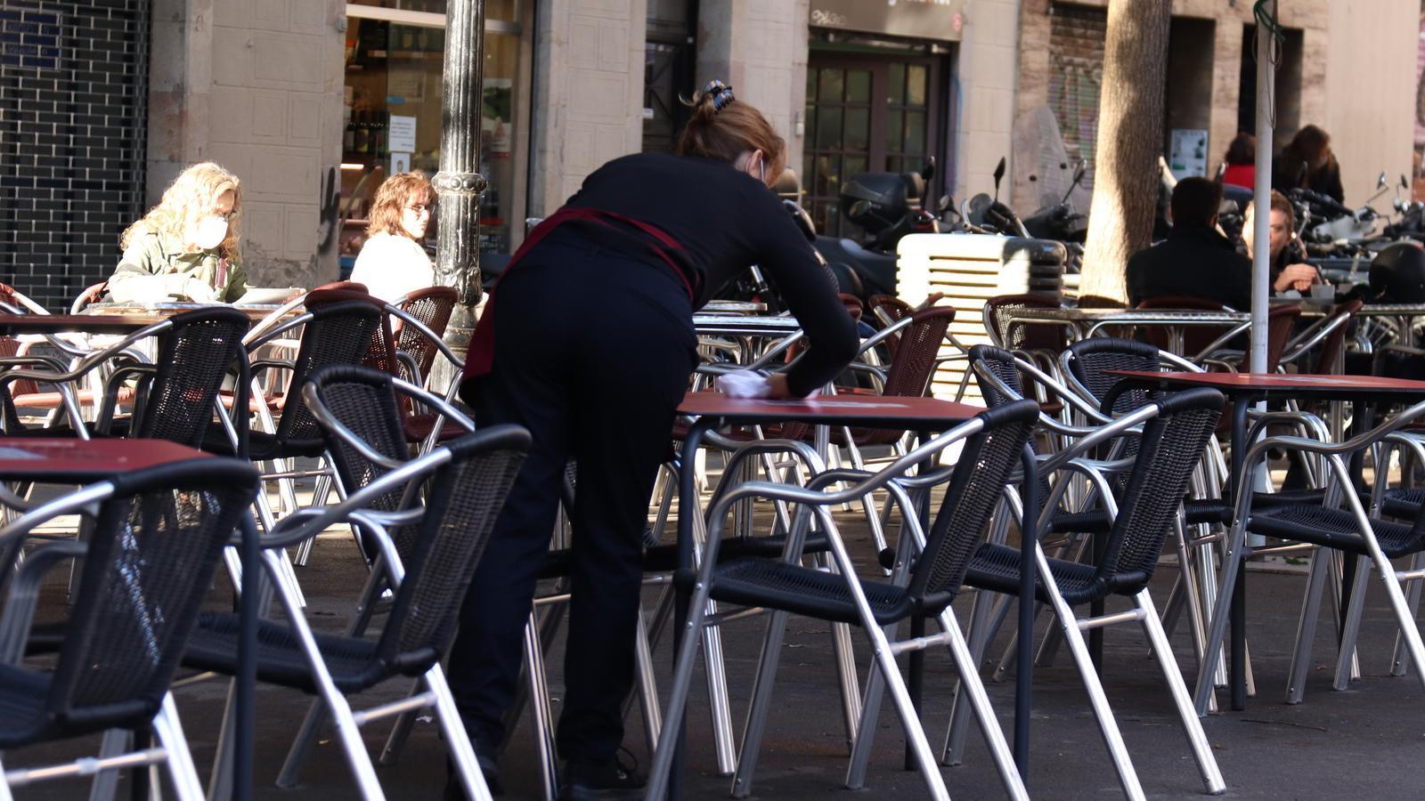Una cambrera neteja una taula aquest dilluns al matí en una terrassa al barri de Gràcia, a Barcelona.