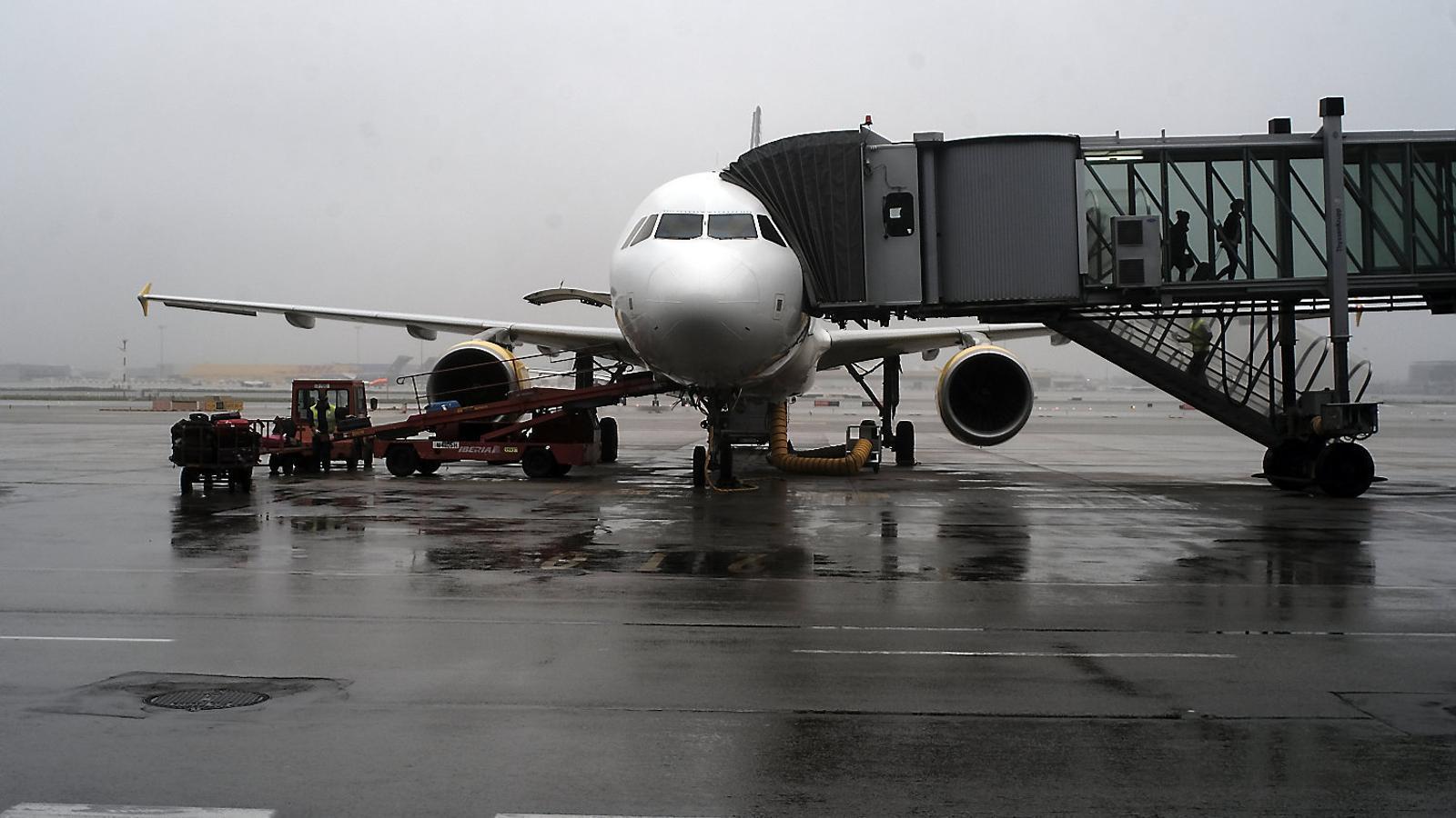 Un avió de Vueling aturat a l'aeroport del Prat en un dia de pluja.