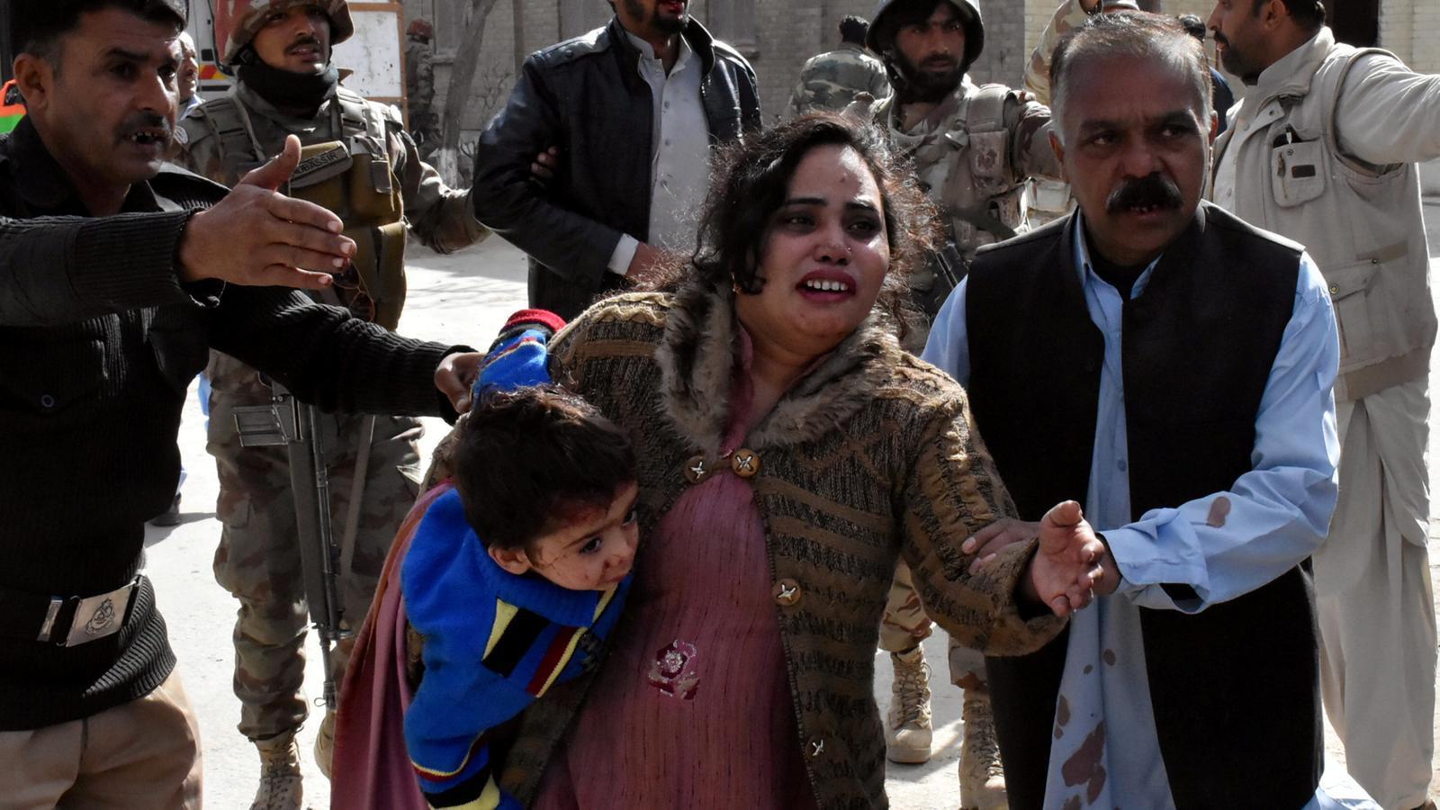 Un policia pakistanès guia una familia lluny de l'esglèsia on s'ha produït el tiroteig