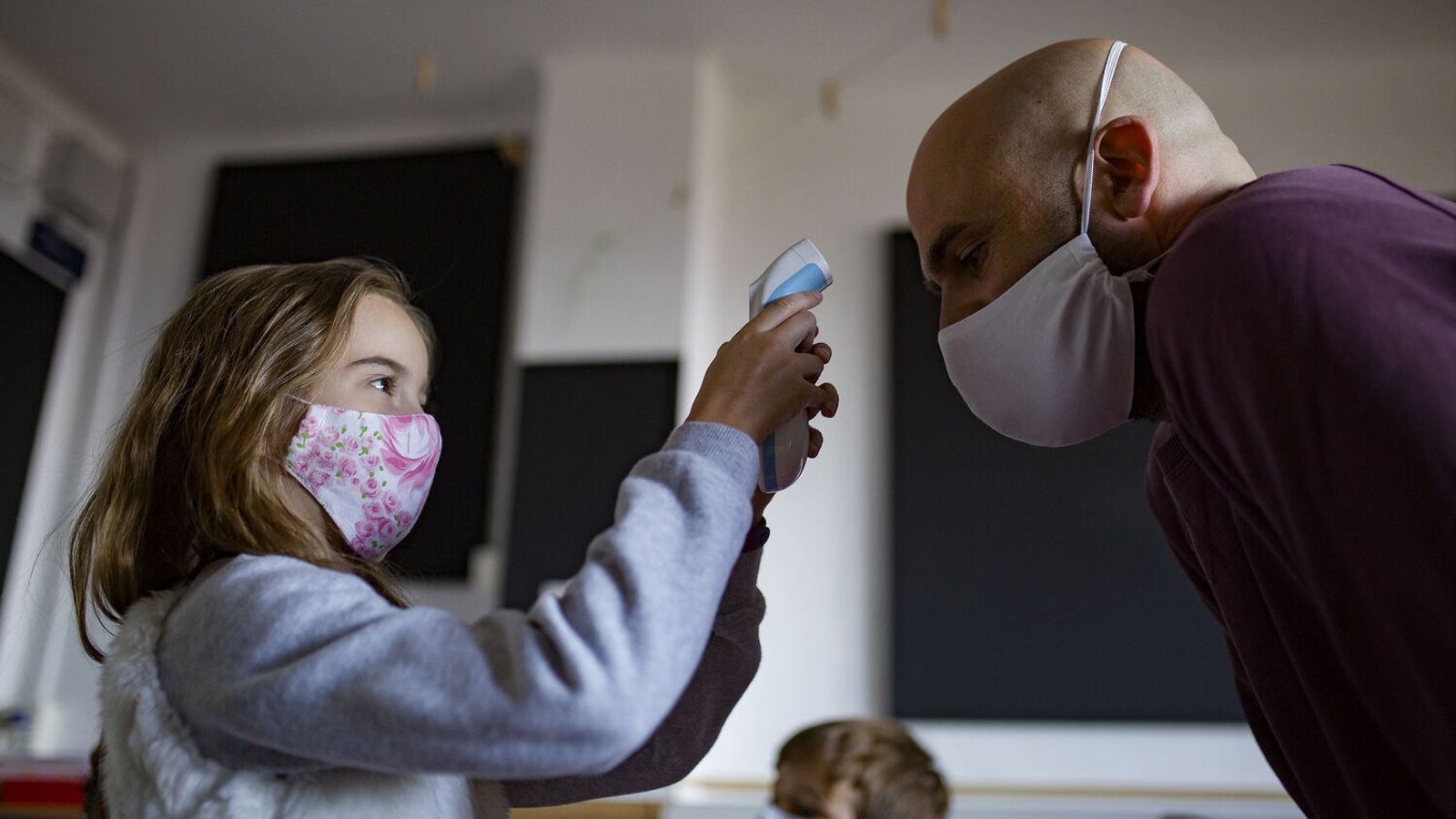 Una nena prenent la temperatura a un adult.