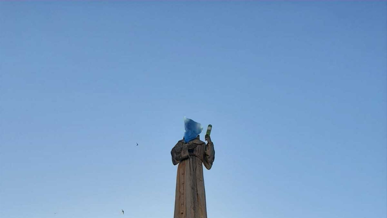L'estàtua del Pare Serra amb la bossa al cap i una botella a la mà esquerra.