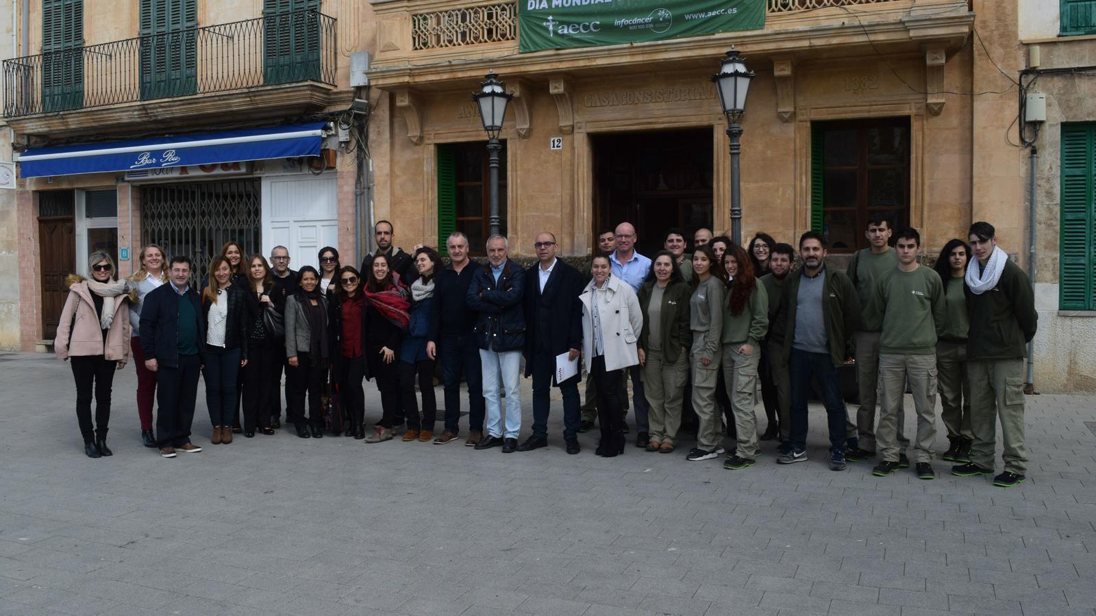 Els beneficiaris dels cursos formatius amb membres de l'equip de govern, davant la casa consistorial.