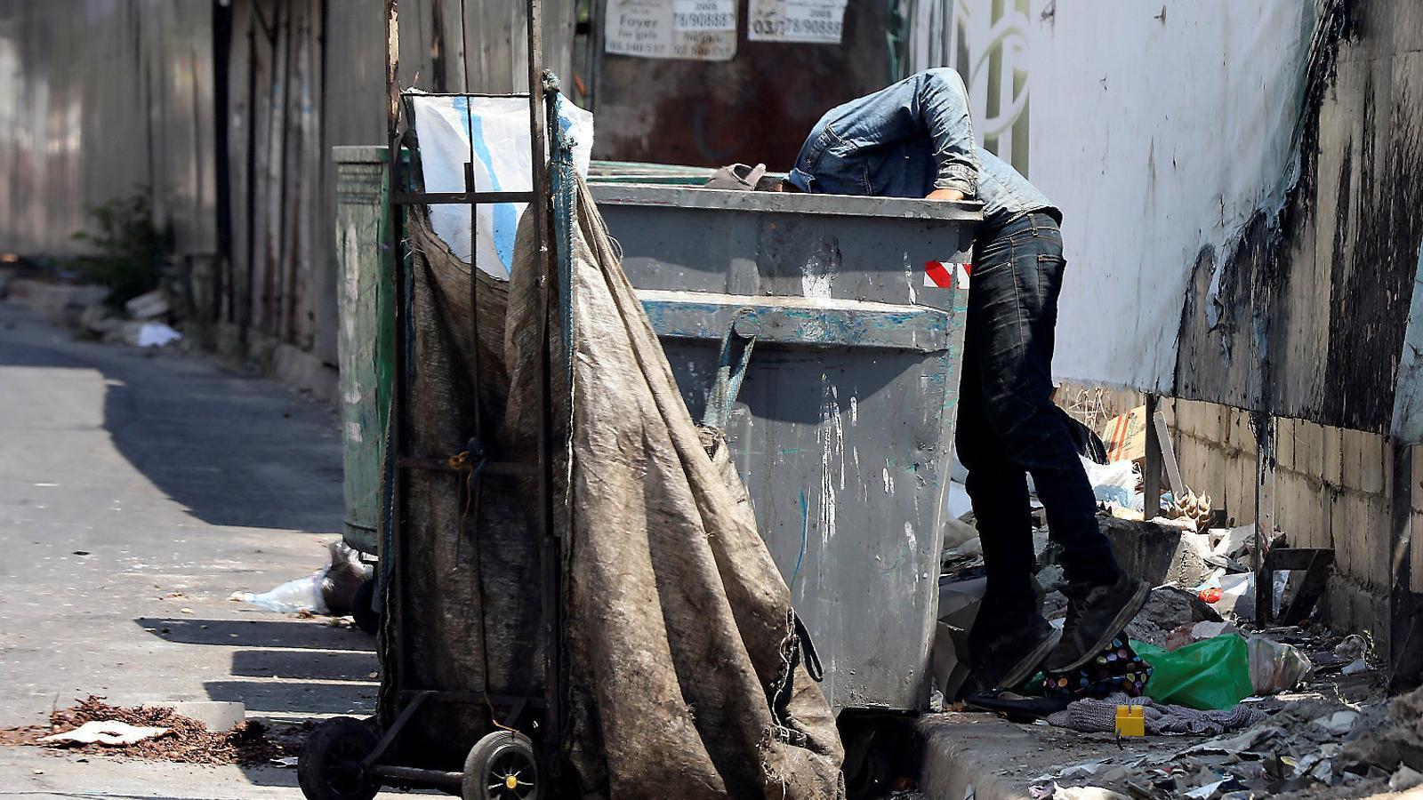 Un home remenant un contenidor d'escombraries en un carrer del Líban.