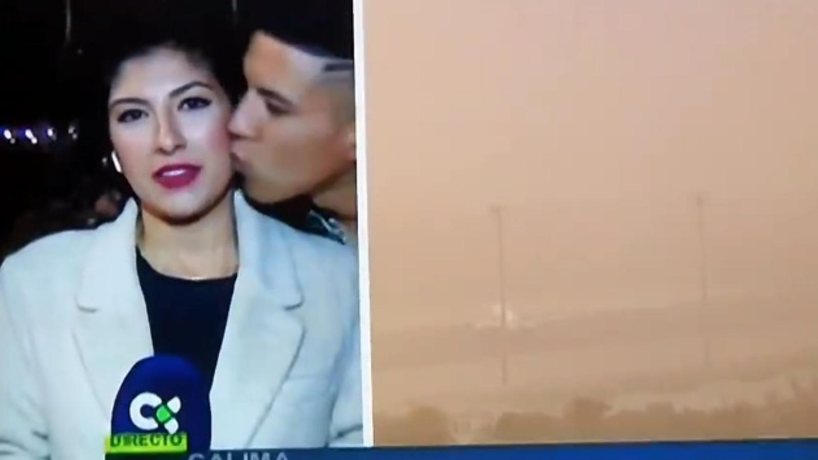 L'home va fer-li un petó a la galta mentre ella informava sobre l'alerta meteorològica