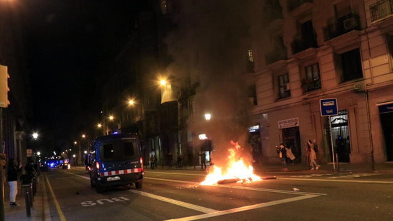 Una furgoneta dels Mossos baixa per Via Laietana al costat d'un patinet cremant