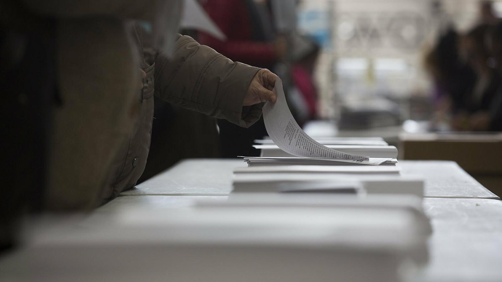 Un ciutadà escollint entre les paperetes dels partits en les eleccions del 21 de desembre passat.