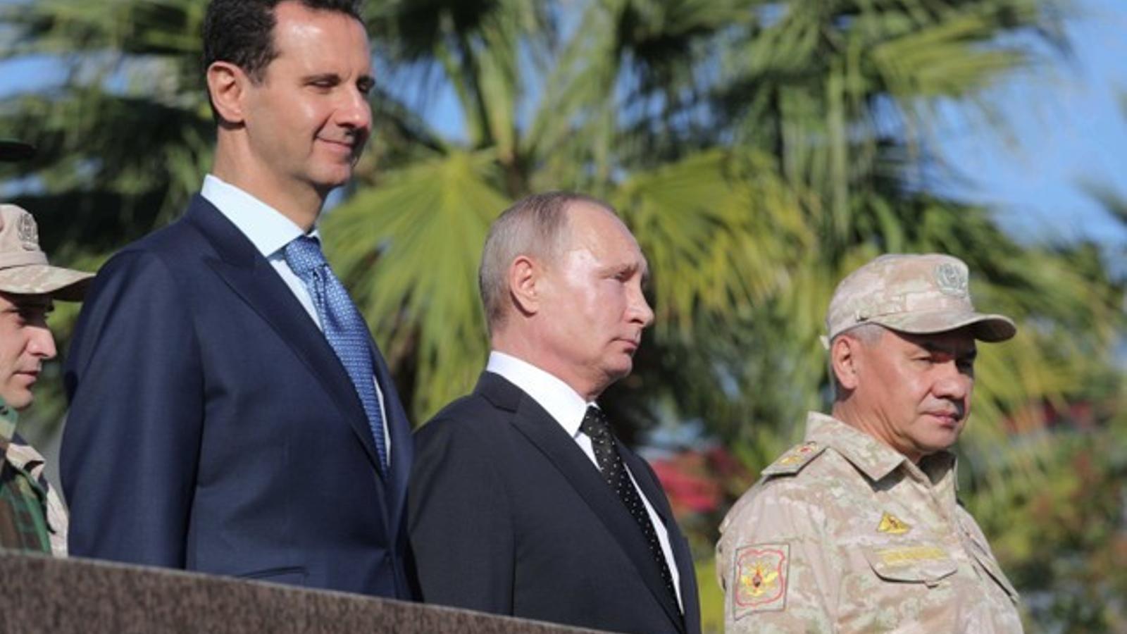 Baixar al-Assad i Putin escolten els himnes a l'arribada a la base aèria de la regió de Latakia.