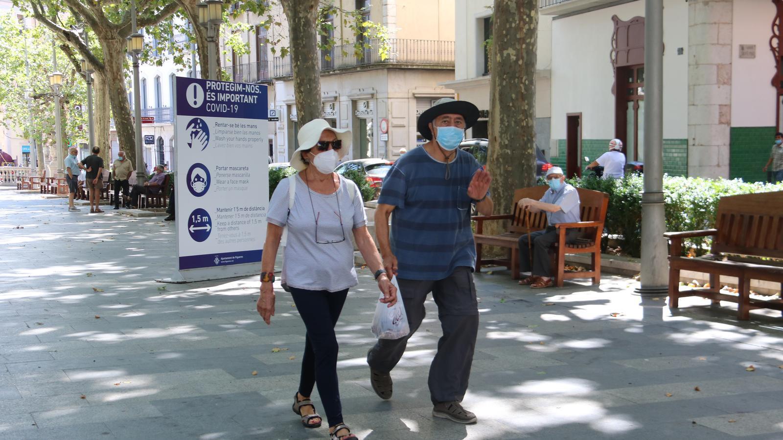 Dues persones amb mascareta passant per davant d'un cartell de recomanacions a la Rambla de Figueres.