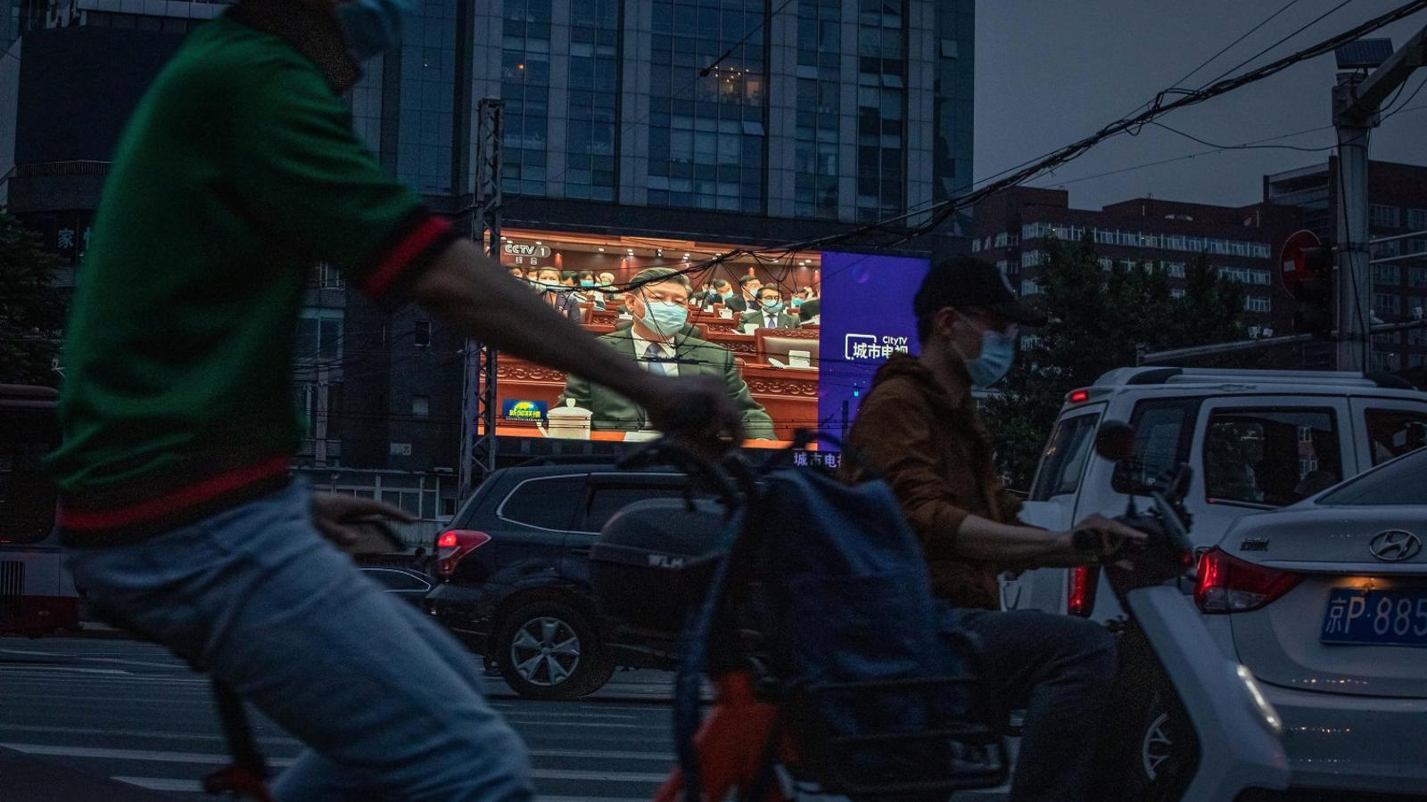 Al fons, una pantalla que mostra el president xinès, Xi Jinping.