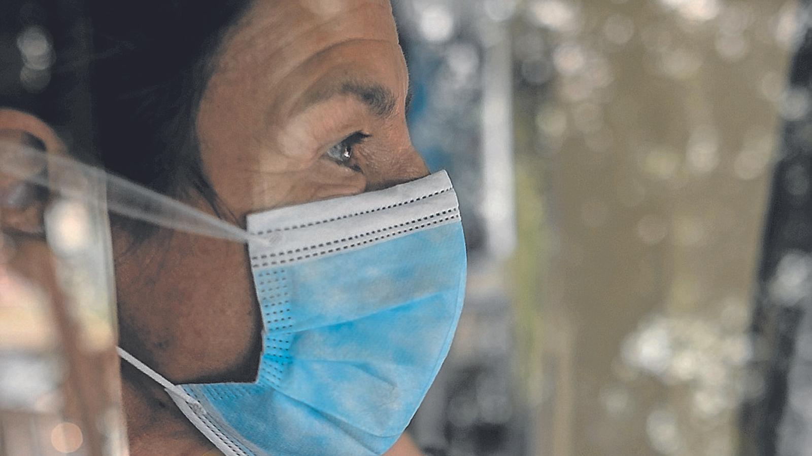 Una dona duu una mascareta quirúrgica a la feina.