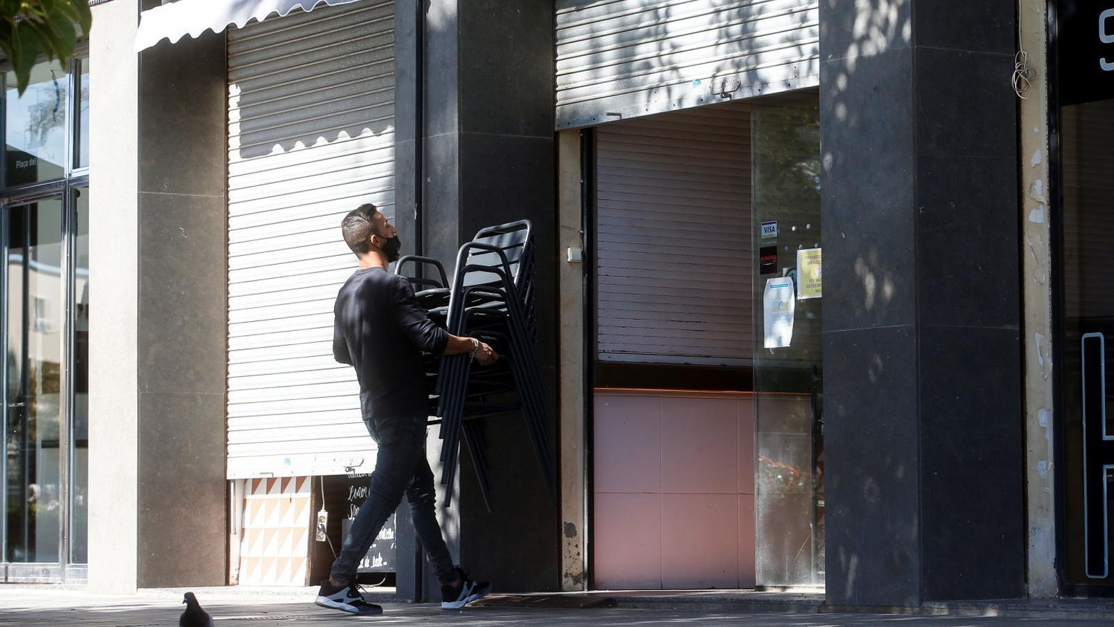 Un home ahir guardant les taules i cadires de la terrassa a l'interior d'un establiment de restauració al barri de la Barceloneta.