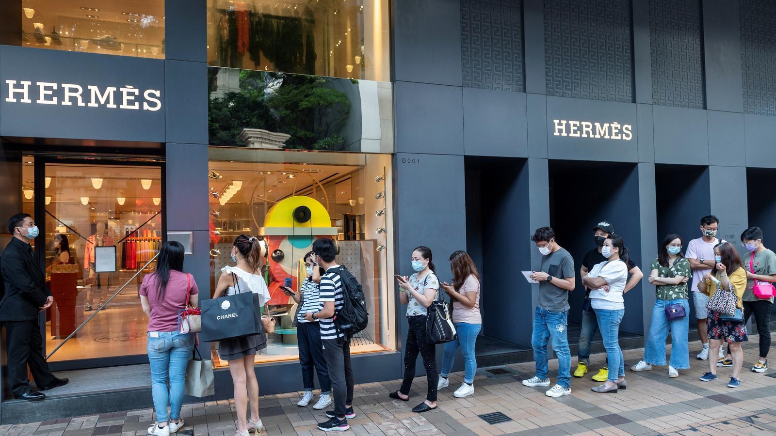 Compradors fan cua davant de la botiga d'Hermès de Hong Kong