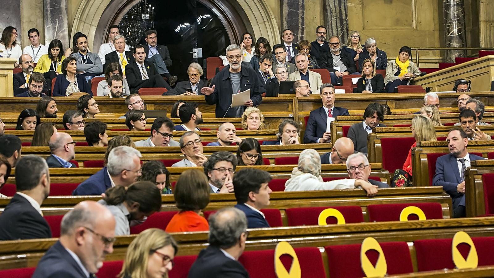 Quim Torra d'esquena en primer pla escoltant l'última intervenció de Carles Riera en el debat d'investidura.