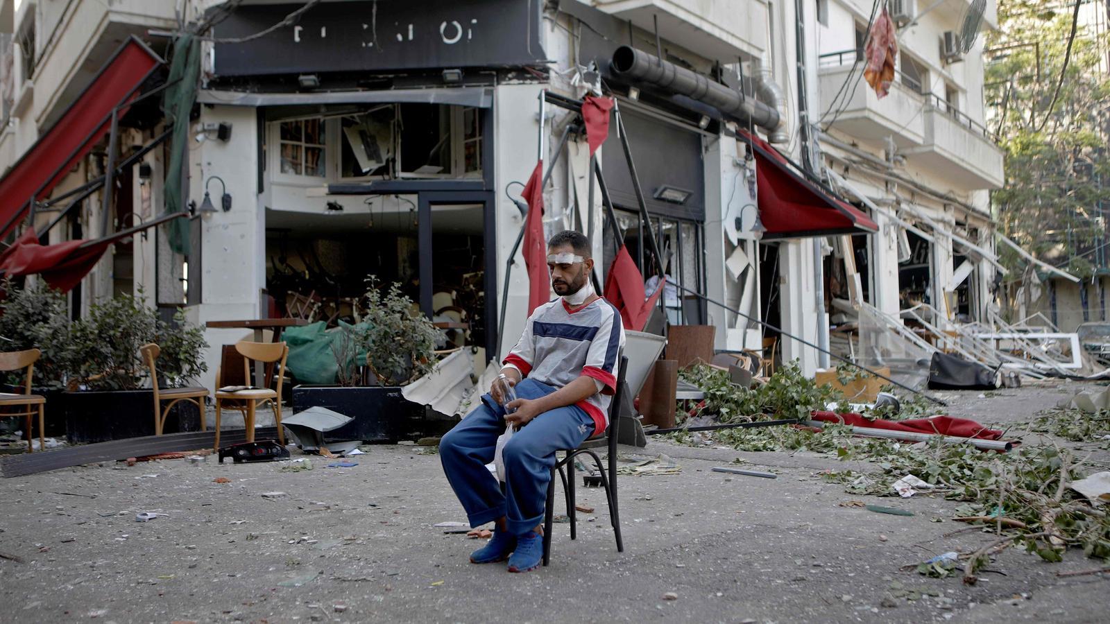 Un home ferit s'assenta al costat d'un restaurant del barri de moda de Beirut, Mar Mikhael