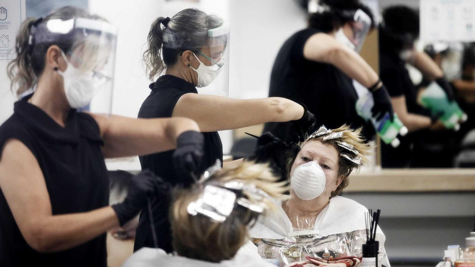 Comencen a atendre els primers clients en una perruqueria del barri de Sants de Barcelona