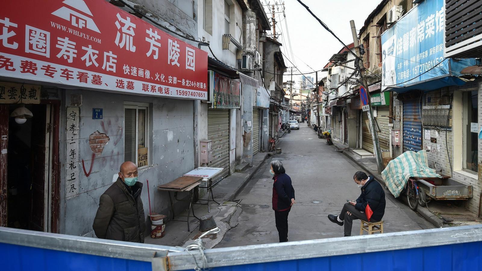 Persones davant d'una barrera per evitar l'entrada de gent a un barri de Wuhan, Xina