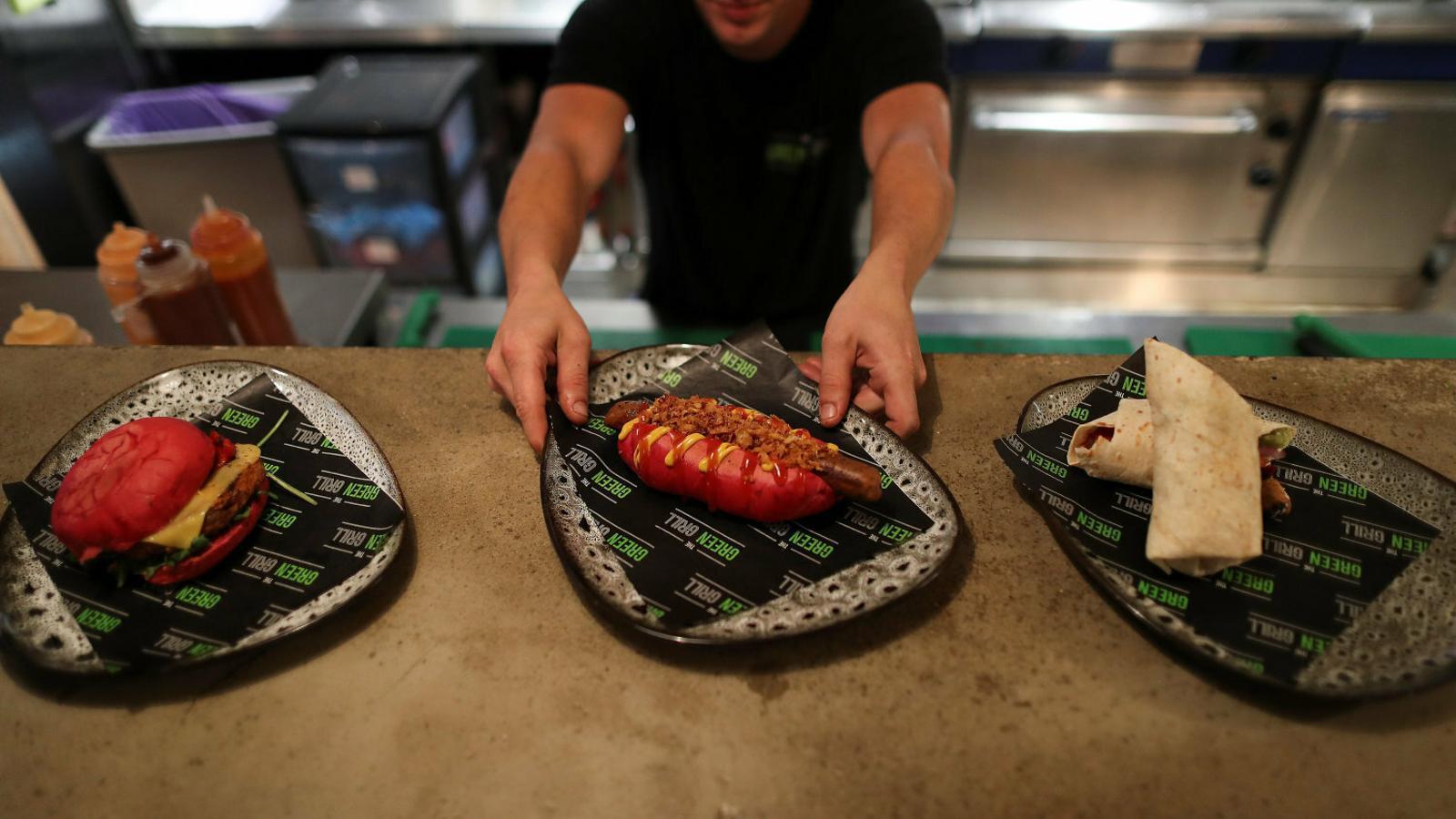 01. Un cambrer servint plats vegans en un restaurant de Londres. 02. Una hamburguesa vegana.