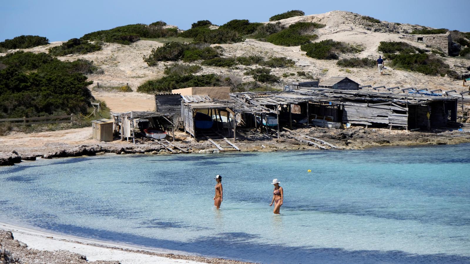 Dues banyistes a la platja de les Illetes de Formentera, gairebé buida aquest dilluns en el primer dia de la fase 1 del desconfinament