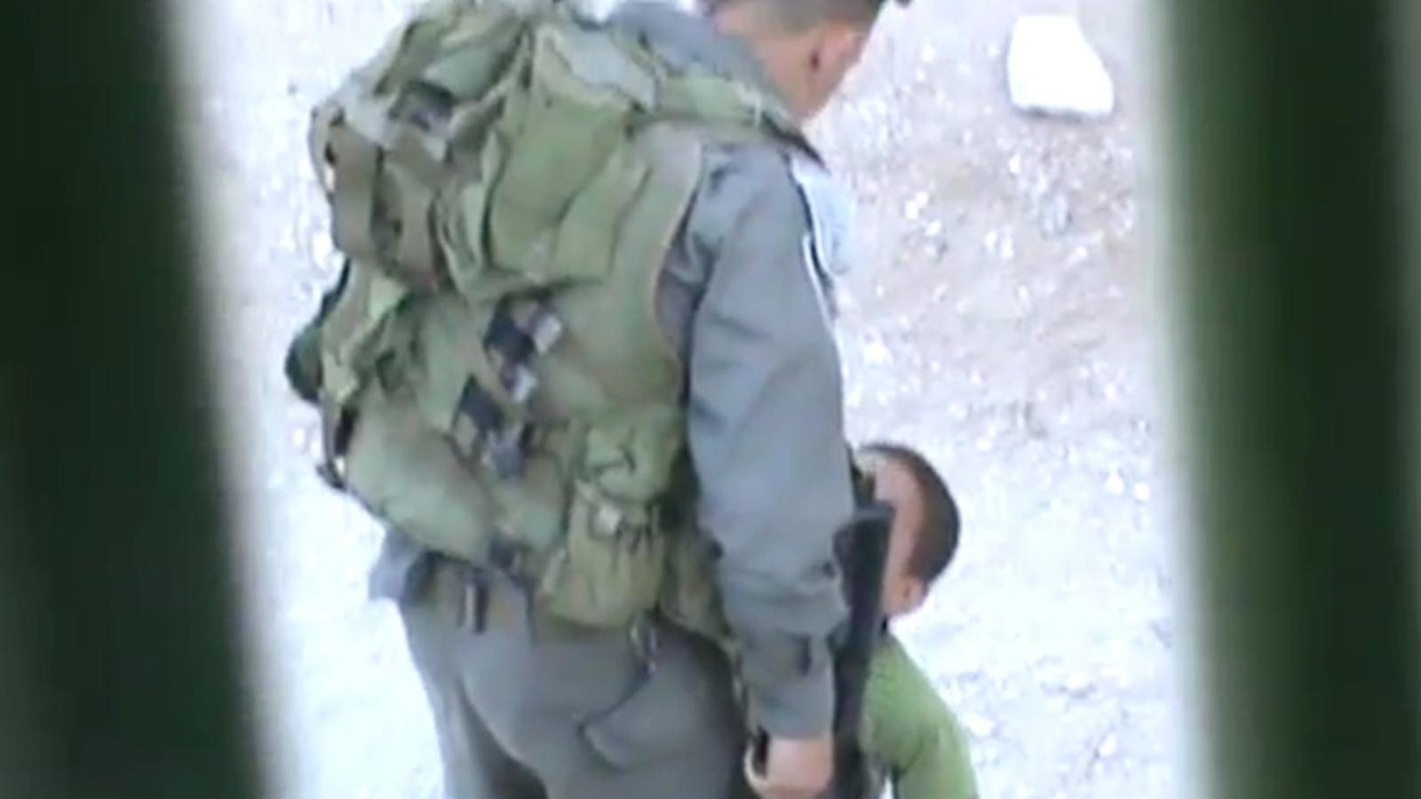 Un policia israelià agradeix un nen palestí a Hebron