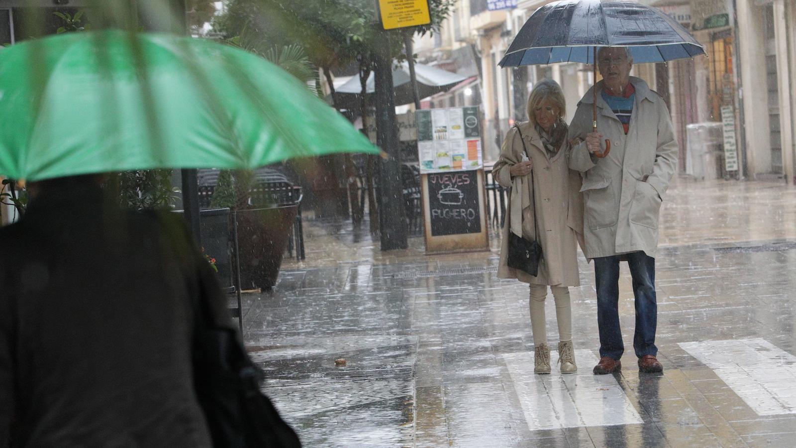 Una parella es protegeix de la pluja que cau a la localitat valenciana de Gandia