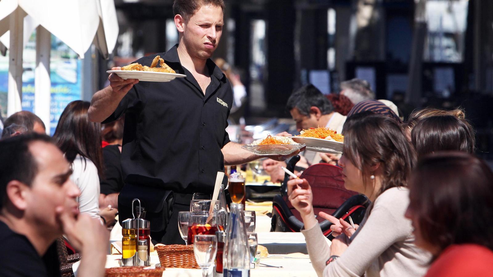 Un cambrer serveix dinars en un restaurant del centre de Platja d'Aro, al Baix Empordà.