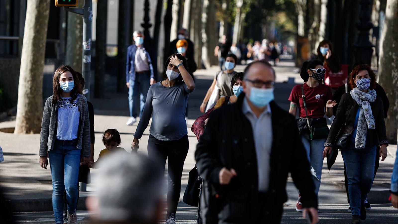 Ambient de gent caminant per Barcelona amb mascaretes.
