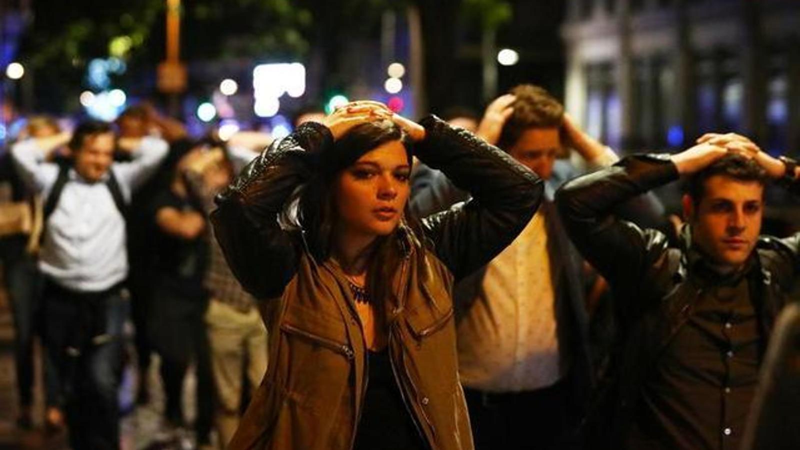 Un grup de persones abandona la zona del London Bridge amb els braços alçats. / NEIL HALL / REUTERS
