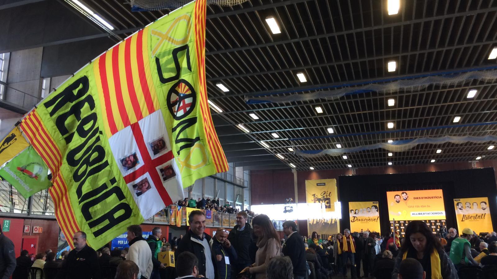 Un dels membres de l'ANC oneja una bandera amb les cares dels presos i el missatge 'Som República'