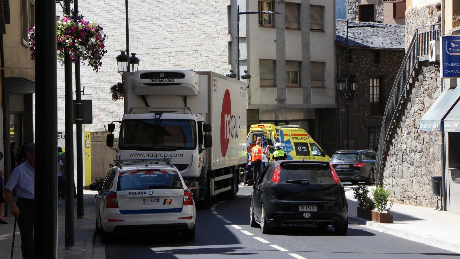El camió estacionat al costat esquerra de la calçada i el vianant sortint de l'ambulància, en el lloc dels fets. / C. A.