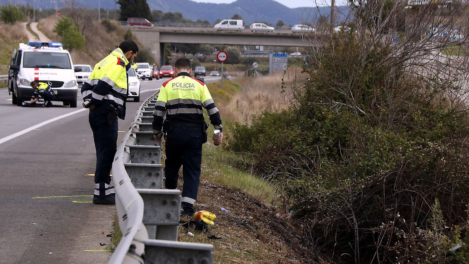 Dos agents dels Mossos d'Esquadra inspeccionant el punt de la carretera C-31, a Vilanova i la Geltrú, on dissabte van morir els dos ocupants d'una moto en un xoc frontal amb un turisme.