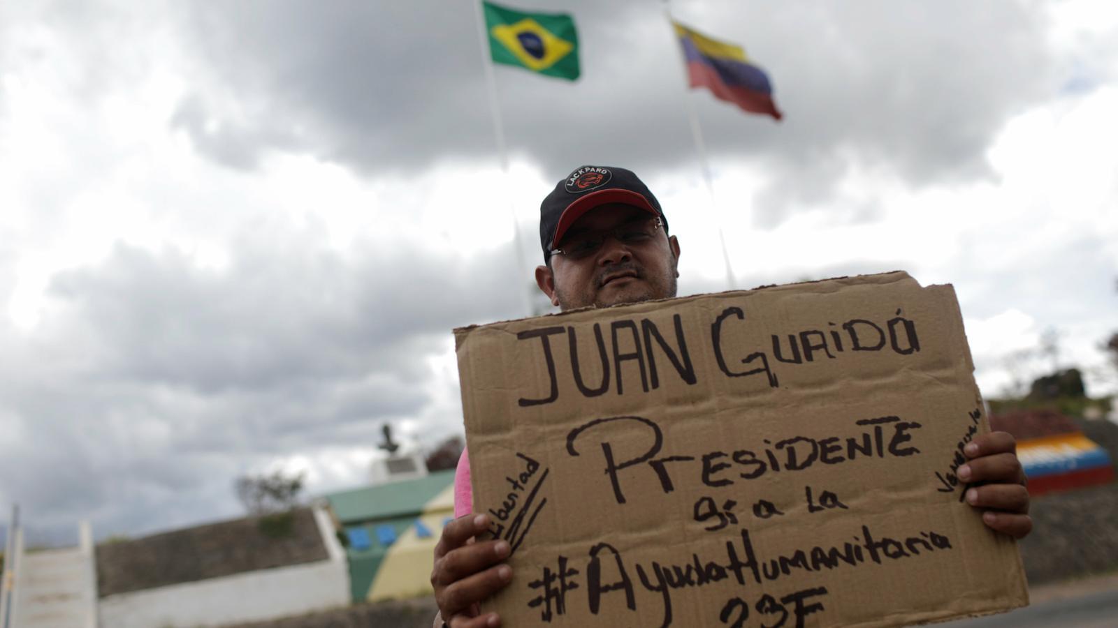 Un veneçolà mostrant un cartell en suport a Juan Guaidó, al municipi brasiler de Pacaraima
