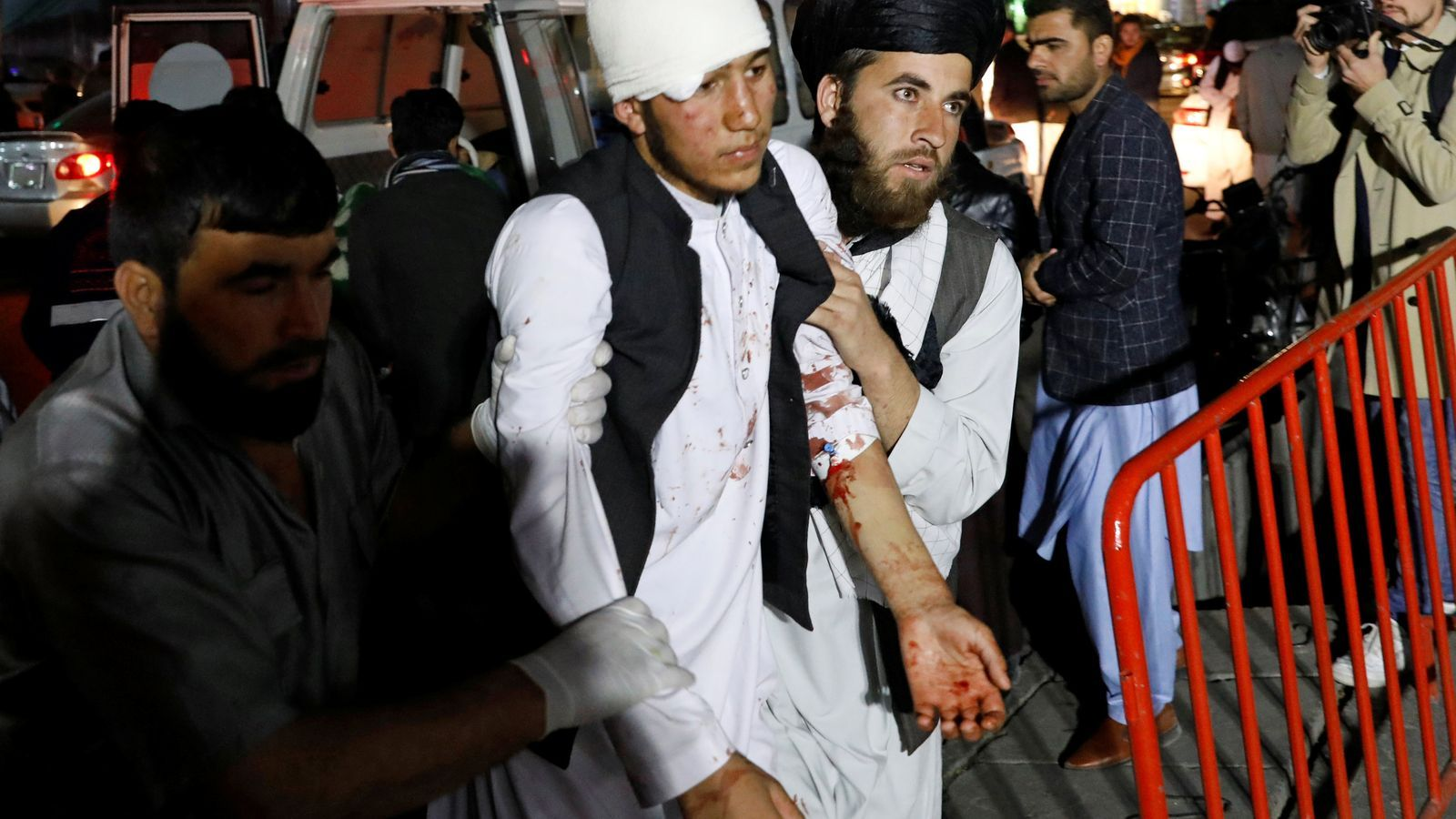 Dos homes afganesos sostenen un supervivent de l'atemptat suïcida de Kabul.