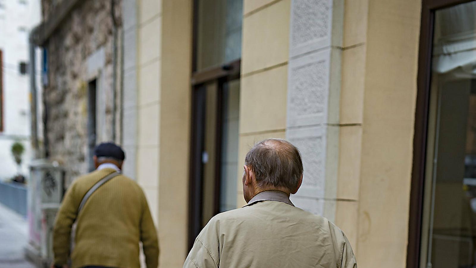Dos homes de la tercera edat passejant per Barcelona.