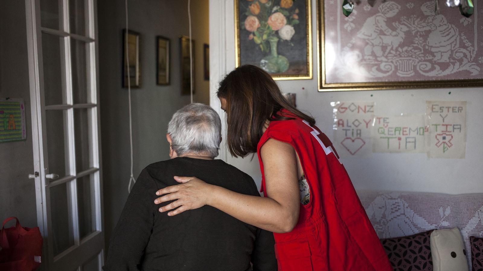 Usuària de la Creu Roja assistida per una voluntària de la Creu Roja en una foto d'arxiu.
