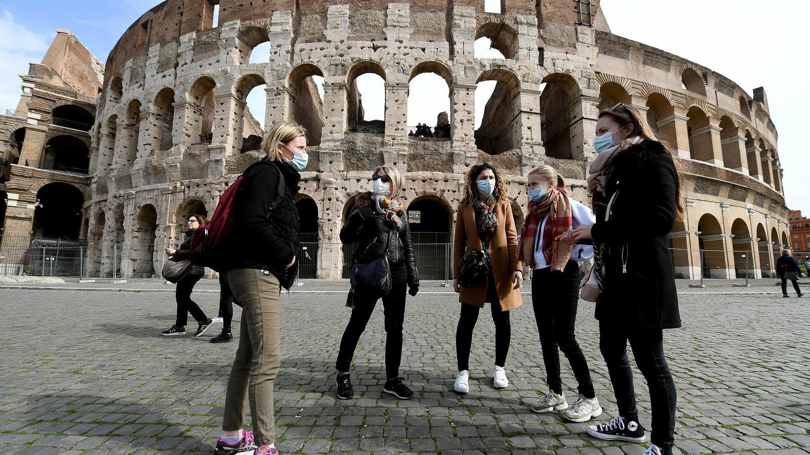Joves amb mascareta davant del Coliseu de Roma