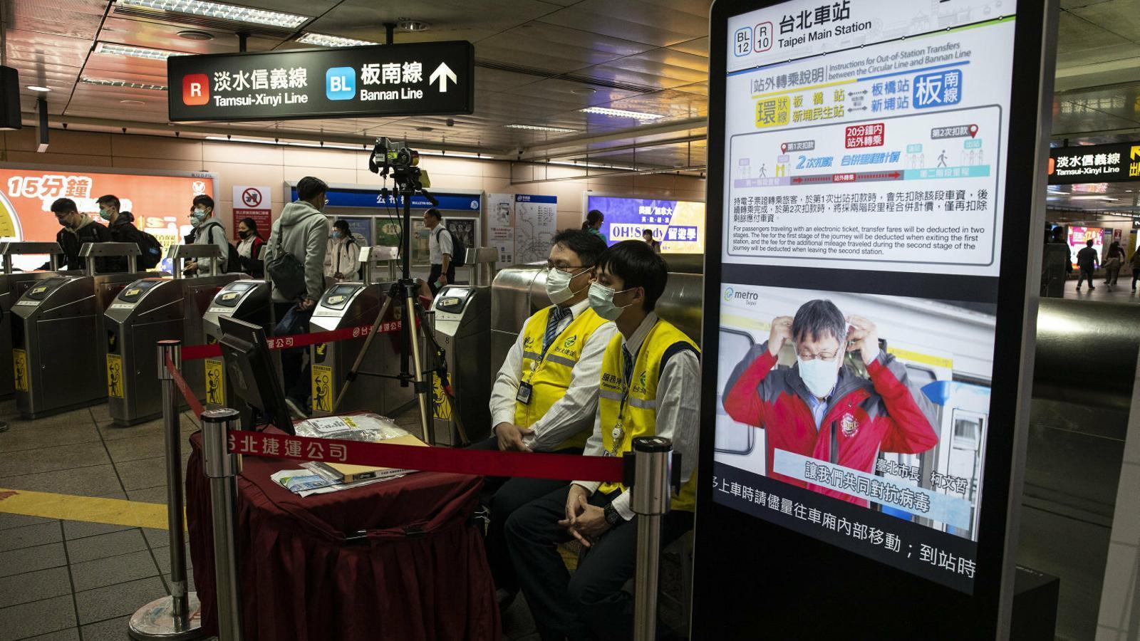 Personal del metro de Taipei controlant la temperatura  dels passatgers que hi entren amb un escàner tèrmic.